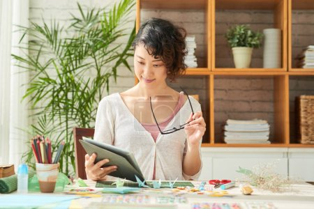 woman designer holding digital table at table with decor