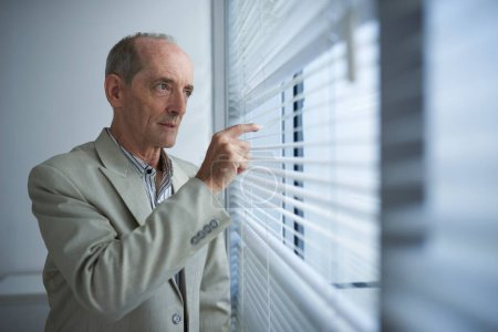 Curious senior businessman looking outside through blinds