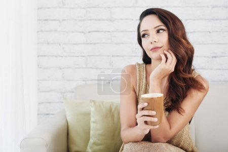 dreamy charming young woman with wavy hair sitting on sofa and holding mug