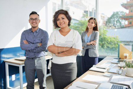 Photo for Cheerful Vietnamese business lady and her coworkers in office - Royalty Free Image