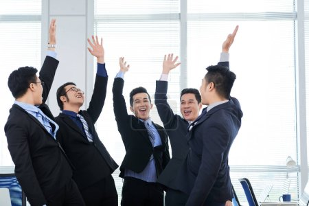 Group of cheerful managers wearing classical suits standing in circle and giving high five