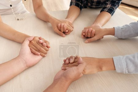 Photo for Group of people supporting each other, holding hands at table - Royalty Free Image