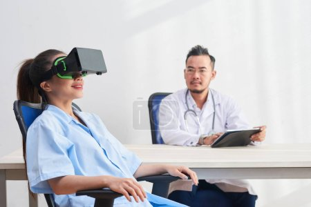 Photo for Young Vietnamese doctor with digital tablet watching female nurse in VR goggles - Royalty Free Image