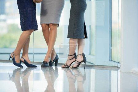 Photo pour Image recadrée de trois femmes d'affaires bavardes debout dans le couloir du bureau, vue partielle des jambes - image libre de droit