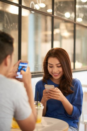 Photo for Asian woman and man sitting in cafeteria with drinks and using phones in separation - Royalty Free Image