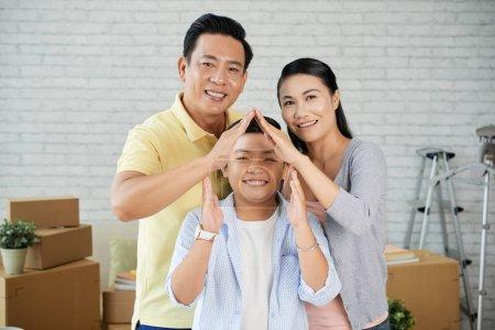 Photo pour Famille asiatique heureuse de trois regardant la caméra avec des sourires toothy et main dans la main en forme de maison - image libre de droit