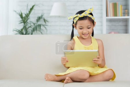 Photo for Smiling Asian little girl reading something on tablet computer - Royalty Free Image
