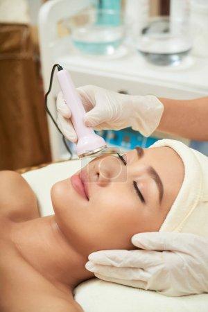Photo pour Esthéticienne mains faisant échographie faciale procédure tandis que jolie asiatique client couché sur la table de traitement avec les yeux fermés - image libre de droit