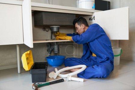 Photo pour Jeune plombier vietnamien vérifier drain dans la cuisine - image libre de droit