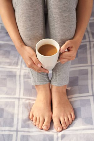 Photo for Cropped image of barefoot female feet on bed, woman holding cup with coffee - Royalty Free Image
