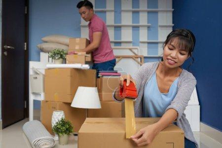 Photo pour Jeune couple asiatique emballage boîtes en carton avec ruban adhésif - image libre de droit