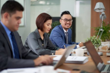 Photo for Asian financial managers analyzing statistic and working in office - Royalty Free Image