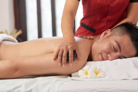 Photo pour Jeune homme asiatique bénéficiant d'un massage aux pierres chaudes dans un salon de spa - image libre de droit