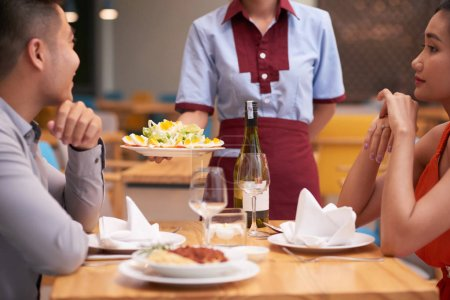 Photo for Cropped image of waitress bringing fresh salad to table - Royalty Free Image