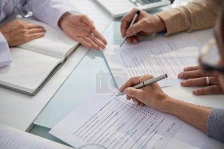 Photo pour Couple âgé assis au bureau et remplissant des formulaires médicaux - image libre de droit