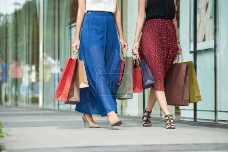 Photo for Cropped image of women with paper-bags walking in the street - Royalty Free Image