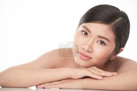 Photo pour Pensive charmante jeune femme asiatique avec une peau impeccable regardant la caméra - image libre de droit