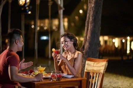Photo pour Souriant asiatique homme divertissant jolie copine avec léger bavardage tout en ayant dîner à la plage restaurant de station tropicale - image libre de droit