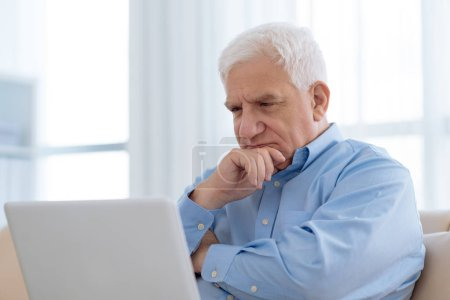 Portrait of pensive aged man looking at laptop monitor screen