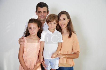Photo pour Famille heureuse de quatre : mère, père, fils et fille posant en studio et regardant la caméra - image libre de droit