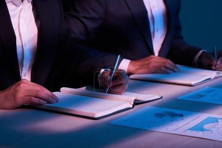 Photo pour Homme d'affaires analysant le tableau financier et prenant des notes dans les journaux - image libre de droit