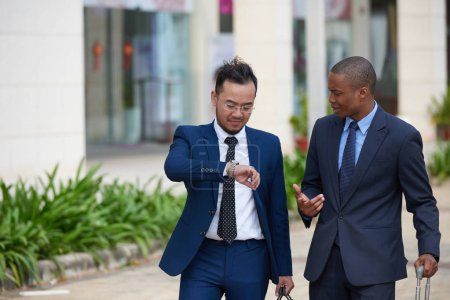 businessmen with luggage bags hurrying to airport and cheeking time on wrist watch
