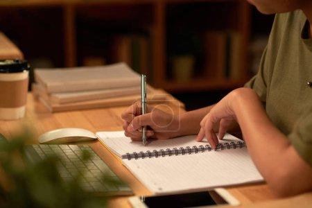 Photo pour Cropped image d'étudiante, essai de rédaction en manuel avec un stylo à tard dans la nuit - image libre de droit