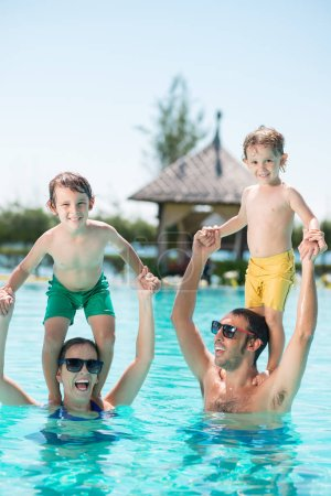 Photo for Happy parent playing with children in swimming pool - Royalty Free Image
