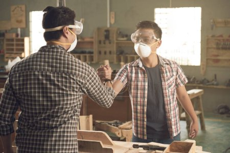 carpenters father and son shaking hands after woodworking in woodworking