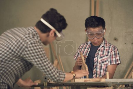 woodworkers, carpenters father and son working with planks in workshop