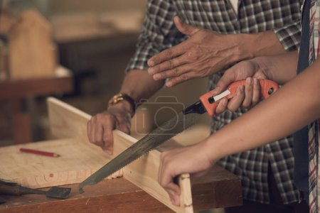 Photo for Carpenters sawing wooden plank with saw, cropped image - Royalty Free Image