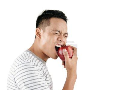 Taille-up Porträt eines jungen asiatischen Mannes, der schmerzhaft zuckt, während er frischen roten Apfel vor weißem Hintergrund isst, Kopierraum