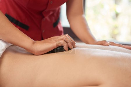 Photo for Close-up of man getting a back massage with hot stones at wellness center - Royalty Free Image