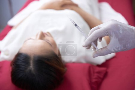 Close-up of doctor holding syringe with collagen liquid and is going to do rejuvenation procedure