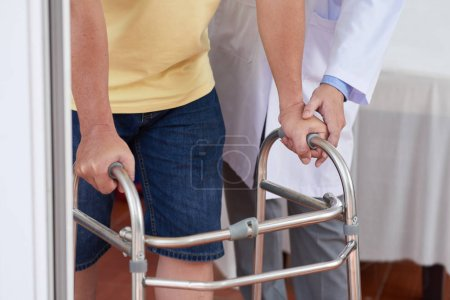 Photo for Unrecognizable medical practitioner helping man to use walking frame during rehabilitation session - Royalty Free Image