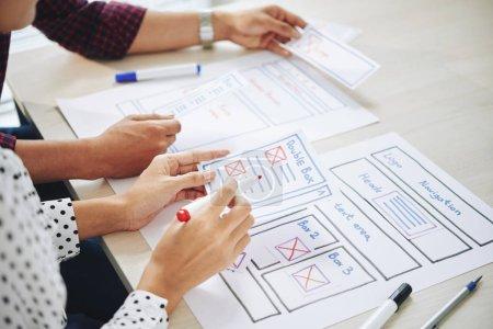 Photo pour Équipe de concepteurs d'interface utilisateur discutant d'idées pour l'interface du site Web lors de la réunion - image libre de droit