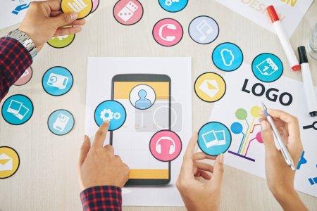 Photo pour Designers discutant ensemble d'icônes pour application mobile, vue d'en haut - image libre de droit