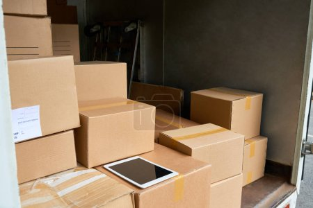 Photo for Many cardboard boxes and digital tablet on delivery box - Royalty Free Image