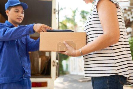 Photo pour Femme prise ordinateur parcelle et tablette de signer pour la livraison - image libre de droit