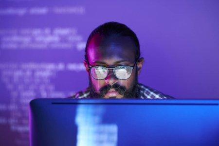 junger seriöser Programmierer mit Brille, der sich auf die Arbeit mit verschlüsselten Daten auf dem Computerbildschirm konzentriert