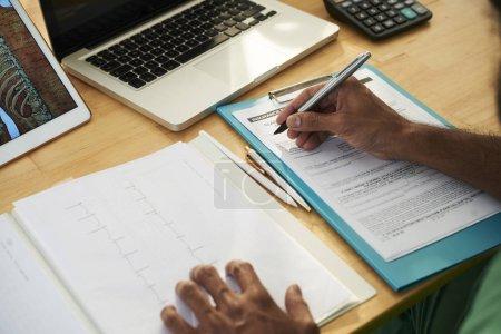Photo pour Mains de professionnel contemporain sur les papiers des notes médicales sur le document d'assurance - image libre de droit