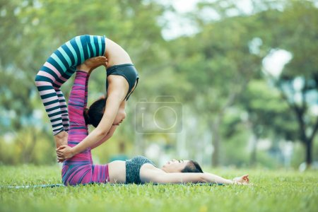Photo for Flexible Asian women practicing acroyoga in park, sport - Royalty Free Image