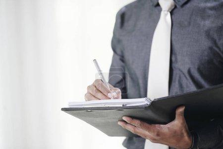 Photo pour Gros plan image d'homme d'affaires en signant des contrats dans le dossier - image libre de droit