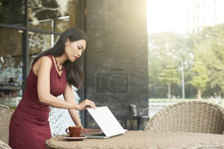 Photo for Young beautiful businesswoman standing and opening her laptop computer for starting the work at the cup of coffee in outdoor cafe - Royalty Free Image