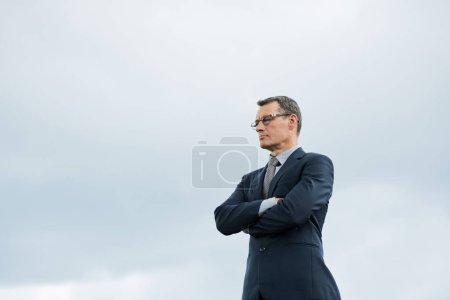 Photo pour Homme d'affaires ambitieux et confiant, les bras croisés contre le ciel - image libre de droit