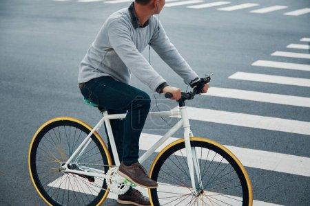 Photo pour Vue latérale de l'homme anonyme vélo le long de la route de la ville et à l'écoute de la bonne musique - image libre de droit