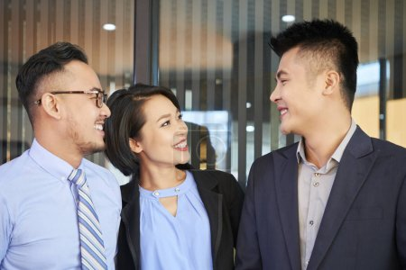 Photo for Smiling Asian business people looking at their successful colleague with admiration - Royalty Free Image