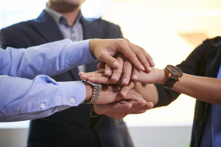 Business people stacking hands to express unity, trust and teamwork