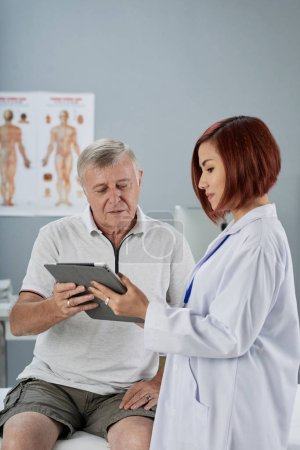Photo for Doctor discussing progress of recovery with senior patient - Royalty Free Image