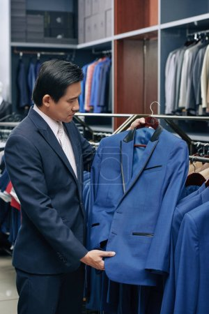 Photo for Vietnamese middle-aged man choosing suit in fashion boutique - Royalty Free Image